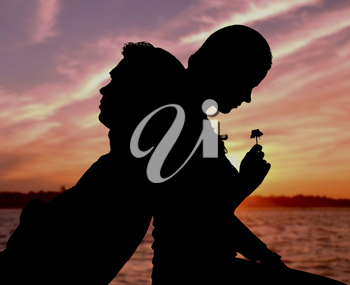 Silhouette of couple sitting back to back on background of sunset