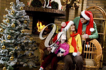 Portrait of happy family wearing santa caps while sitting by fireplace and looking at each other