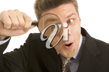 Portrait of businessman looking through a magnifying glass