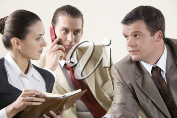 Photo of two colleagues looking at each other during meeting on background of phoning man