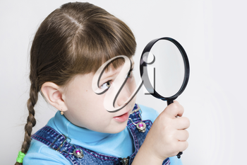 Close-up of small girl holding looking glass in hand and watching through it