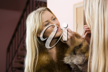 A beautiful young woman making up her lips in front of the mirror