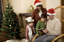 Portrait of family gathered together to read interesting fairy tale with decorated fir tree behind