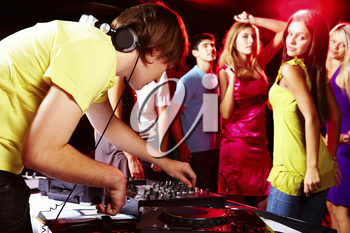 Smart deejay adjusting technics with dancing teens on background