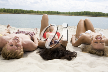 Photo of pretty girls and a guy lying on sandy beach and looking at camera with smiles