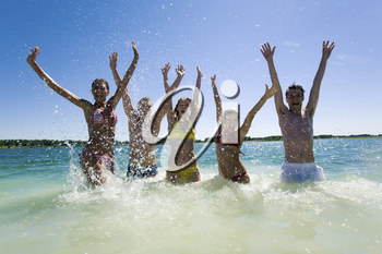 Photo of joyful five people raising their hands while standing in the lake