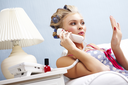 Portrait of female in curlers drying her fingernails and speaking on the telephone