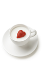 Shot of white cup full of milk with ripe strawberry heart inside