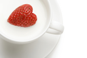 Macro image of heart-shaped strawberry in milk shake
