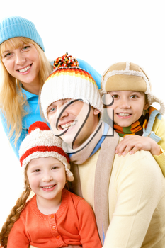 A happy family of four in warm clothes embracing