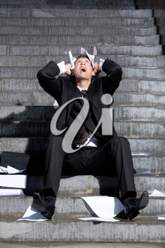 Despaired businessman screaming with papers in hands while sitting on staircase
