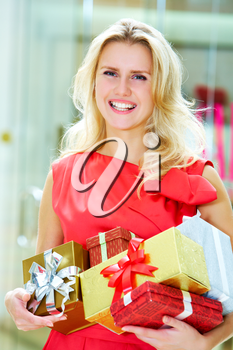 Portrait of pretty woman with giftboxes after good shopping