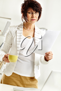 Portrait of middle-aged female reading paper during working day