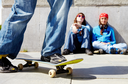 Two teen girls sitting on asphalt and watching their friend skateboarding outdoors
