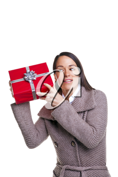 Brunette woman shaking her present to see whats inside, isolated on a white background.