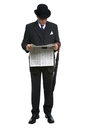 Businessman in bowler hat and three piece pinstripe suit reading a financial newspaper.