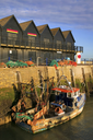 Sunrise in a fishing harbour with buildings and trawler.