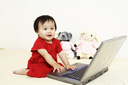 A cute little baby girl playing with a laptop