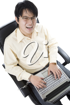 A shot of a businessman handcuffed on a chair working on his laptop