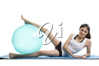 An isolated shot of an asian woman lying down on a yoga mat exercising with a exercise ball