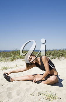 A beautiful caucasian girl stretching before exercise on the beach