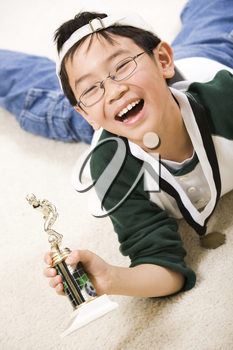 An asian boy excited aboyt his winning sport medal and trophy