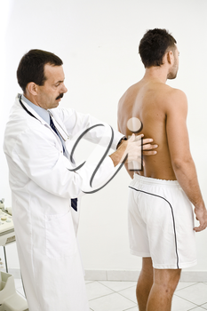 Doctor examining young male patient.