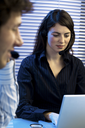 Two young business people sitting at desk, having a teleconference, talking on headset.
