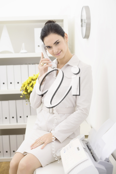 Young businesswoman wearing beige suit talking on landline phone in office, smiling.