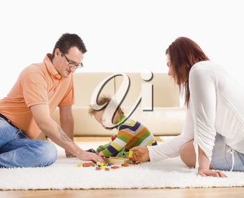 Family with baby boy ( 2 years old ) sitting on floor at home and playing together.
