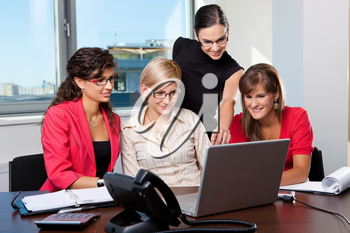 Young businesswomen sitting at table in meeting room, using laptop computer, smiling.