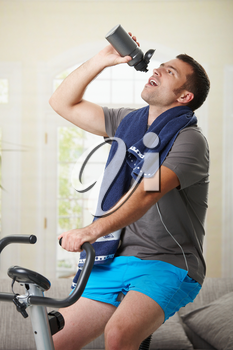 Man sitting on stationary bike at home and drinking water from bottle.