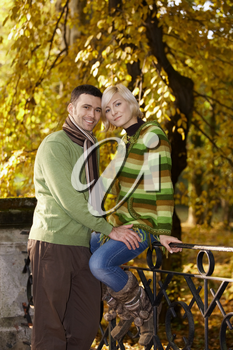 Portrait of happy couple in autumn park. Woman sitting on railing, leaning to each other, smiling.