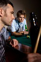 Two men concentrating on playing snooker, drinking beer at game.