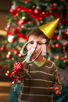 Little boy in new year's eve hat blowing horn, looking at camera.