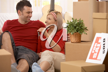 Happy couple sitting in middle of boxes smiling, holding keys of new house.