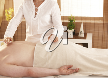 Hands over patient't back during reiki treatment.