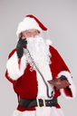 Portrait of Santa on the phone, looking up, isolated on gray background.