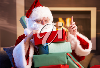 Portrait of Santa Claus sitting by fireplace holding a pile of Christmas presents.