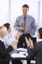 Businesspeople clapping hands, celebrating success of businessman holding glass of champagne.