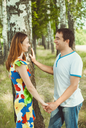 Young happy couple holding hands in the park in the summer.