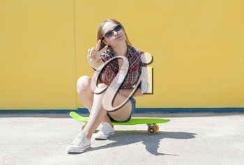 Stylish cheerful young girl with skateboard resting on the street.