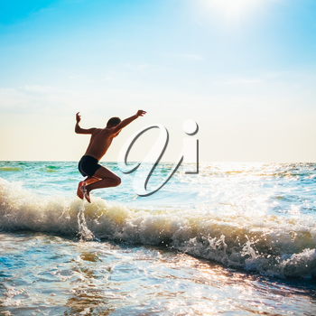 Boy Jumping In Sea Waves. Jump Accompanied By Water Splashes. Summer Sunny Day, Ocean Coast