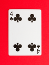 Old playing card (four) isolated on a red background