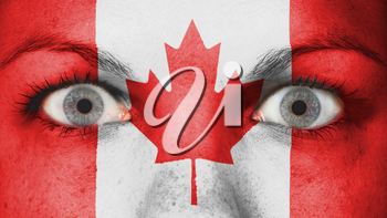 Close up of eyes. Painted face with flag of Canada