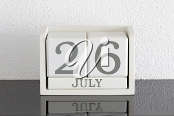 White block calendar present date 26 and month July on white wall background