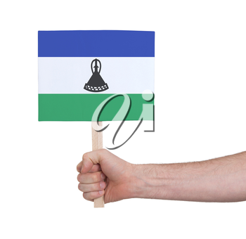 Hand holding small card, isolated on white - Flag of Lesotho