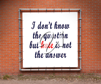 Large banner with inspirational quote on a brick wall - I don't know the question but hate is not the answer