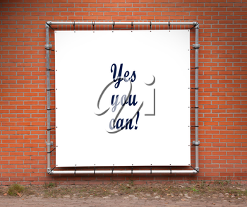Large banner with inspirational quote on a brick wall - Yes you can!