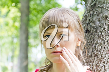 Portrait of thinking girl with blue eyes on green wood background